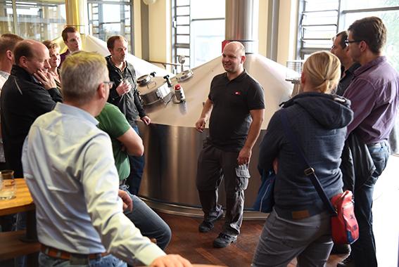 Brauer Christoph Puttnies erklärt den Landwirten, wie Bier gebraut wird.
