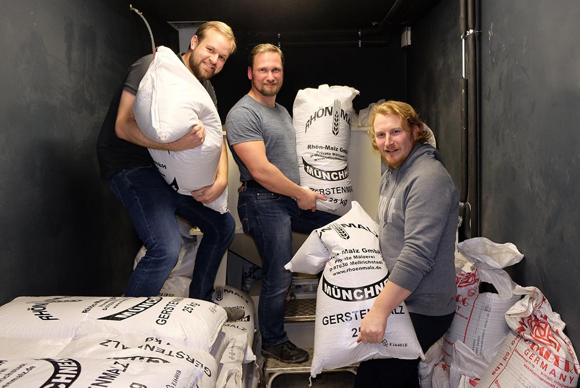 Jens Reineke (Störtebeker Braumanufaktur), Tobias Kandler und Michael Lembke (BRLO) bereiten die Malzschüttung vor.