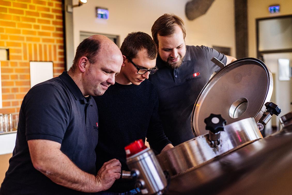 Christoph Puttnies, Nico Leffler und Jens Reineke beobachten die Würze beim Kochen.