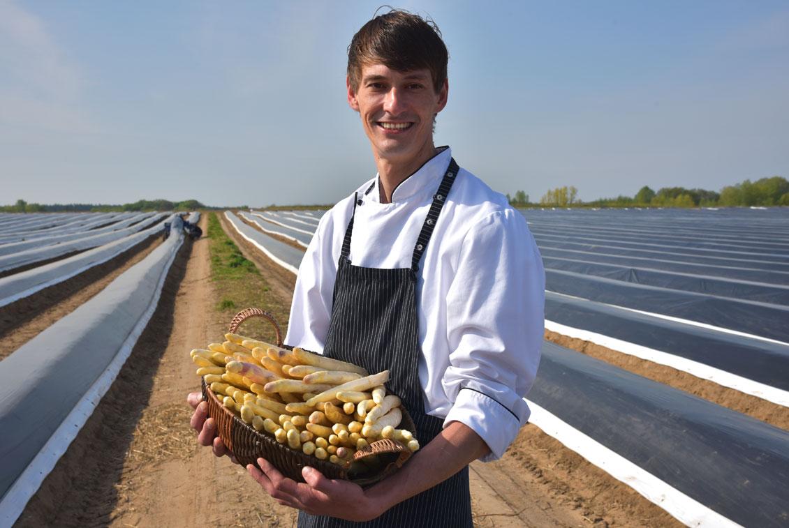 Koch Markus Grugel mit einem Korb frisch gestochenem Spargel.