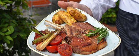 Tomahawk Steak vom Duroc-Schwein Thymiankartoffeln und lauwarmen Balsamico-Lauch-Tomaten